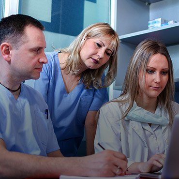 Group of dentists looking at computer