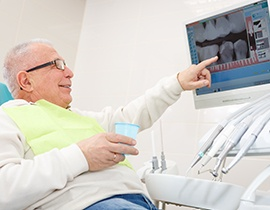 Older man in dental chair pointing to x-rays