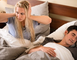 A woman with her hands over her ears and her partner asleep in bed