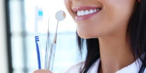 Woman holding teeth cleaning supplies.